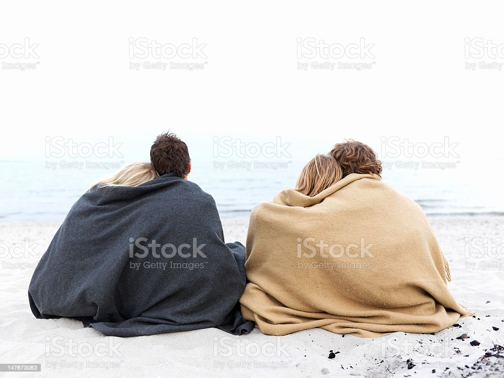 Couples sitting together on the beach in winter royalty-free stock photo