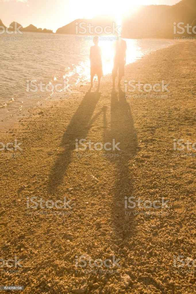 Couples tie the hands on the beach in the evening silhouette and shadow stock photo