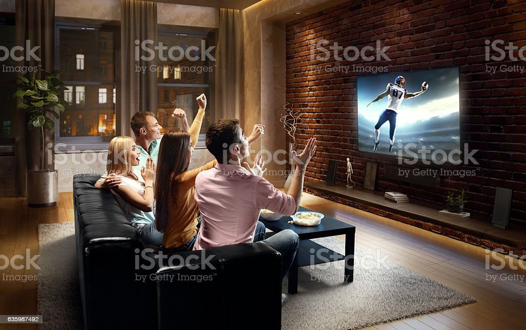 Couples watching American football game at home stock photo