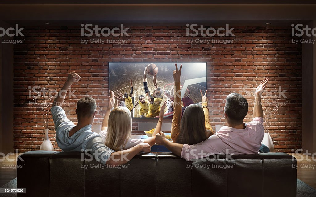 Couples watching Basketball game at home stock photo