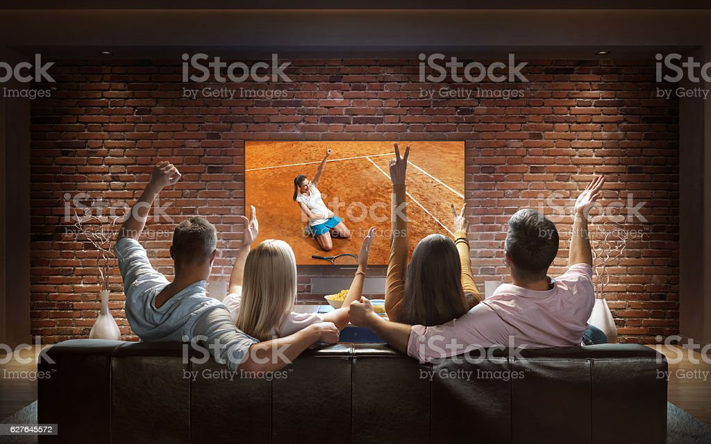 Couples watching Tennis game at home stock photo