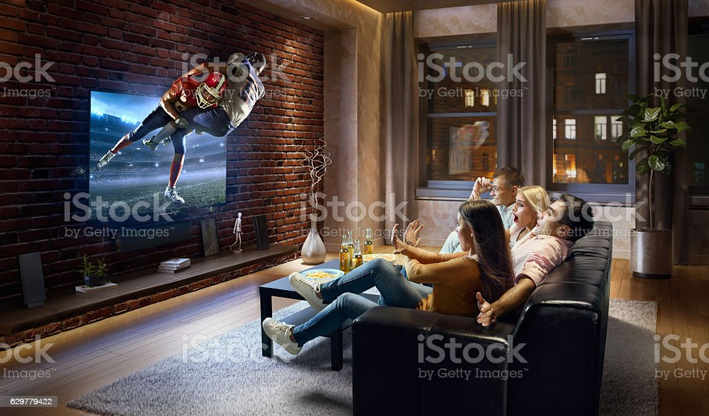 Couples watching very realistic American football game on TV stock photo