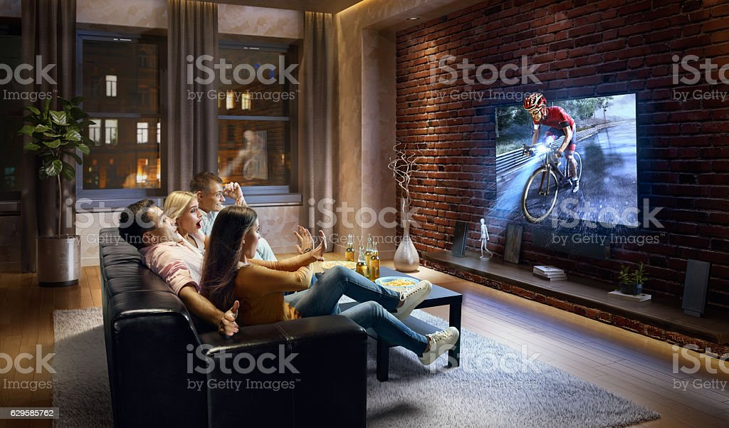 Couples watching very realistic Cycle competition on TV stock photo