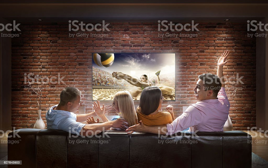 Couples watching Volleyball game at home stock photo