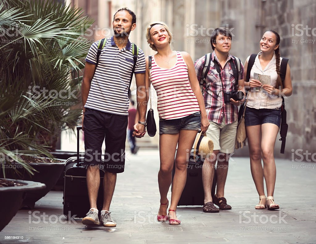 Couples with luggage walking the city stock photo