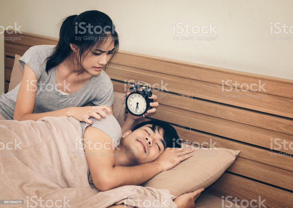 Couples, women motivating men who are asleep, made with a desk clock. stock photo