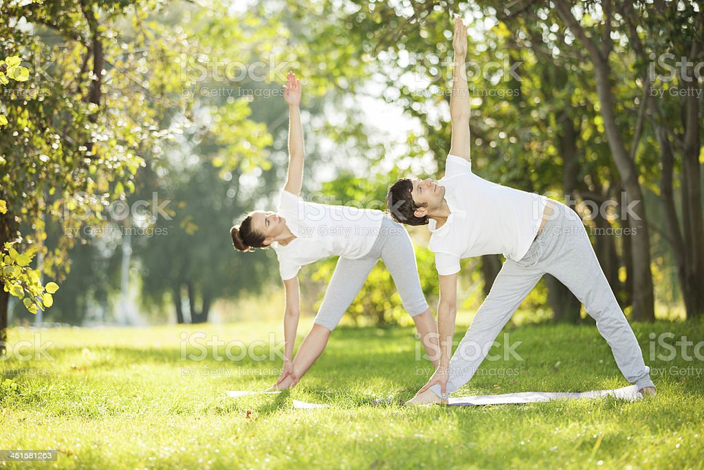 Couples Yoga, man and woman doing exercises in the park stock photo