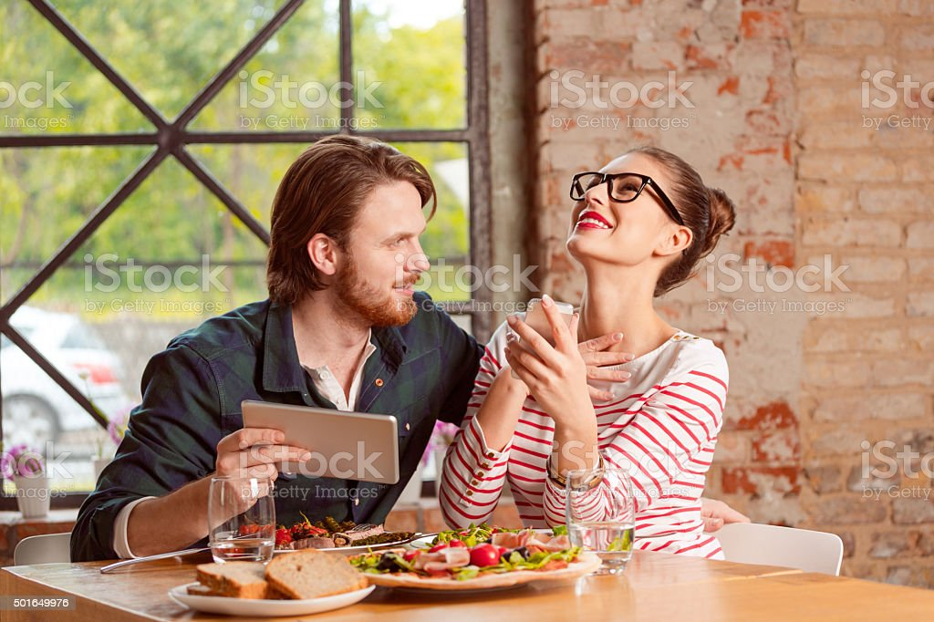 Coupleusing a digital tablet during lunch in the restaurant stock photo