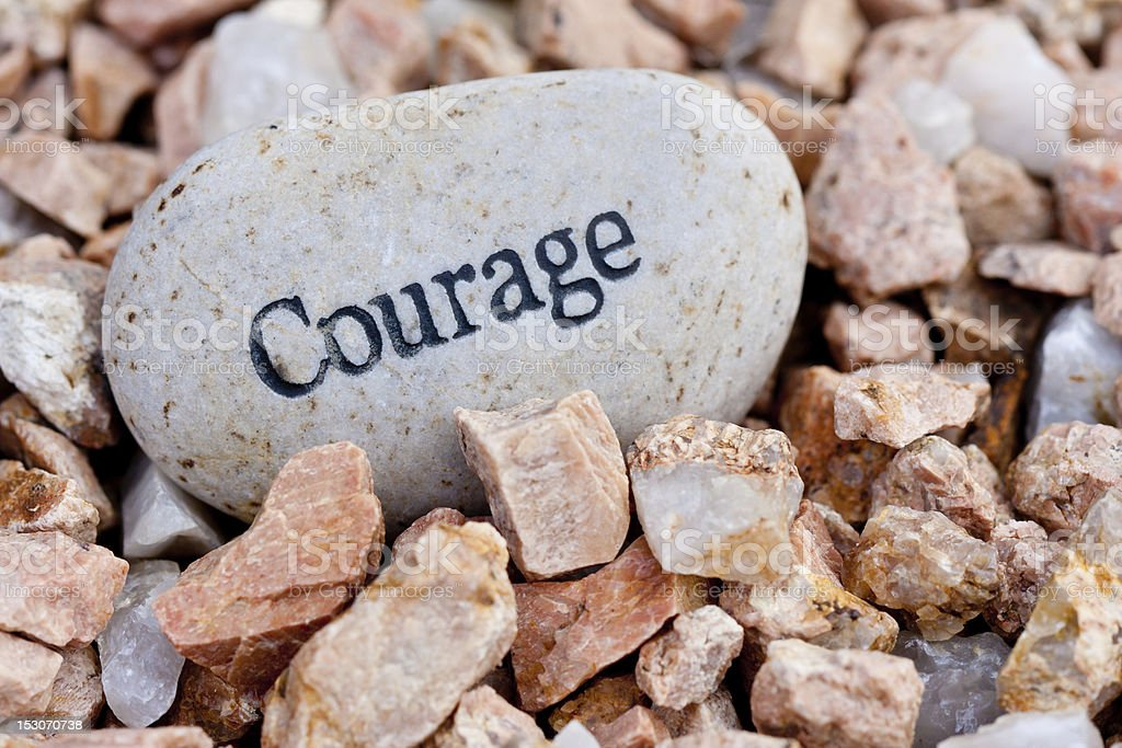 Courage written on a big smooth rock with jagged rocks stock photo