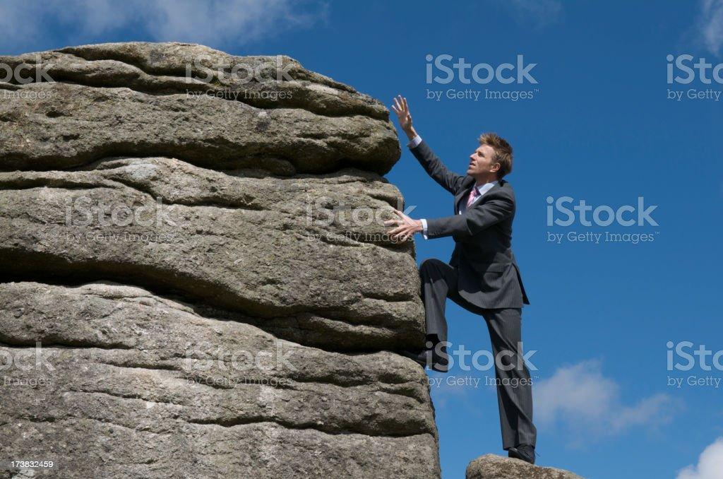 Courageous Businessman Climbing to Top of Mountain Peak royalty-free stock photo