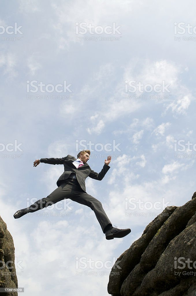 Courageous Businessman Jumping Over Valley stock photo