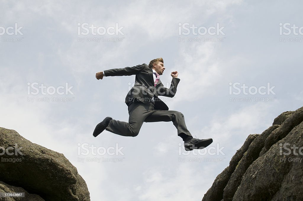 Courageous Businessman Leaping between Rocks stock photo