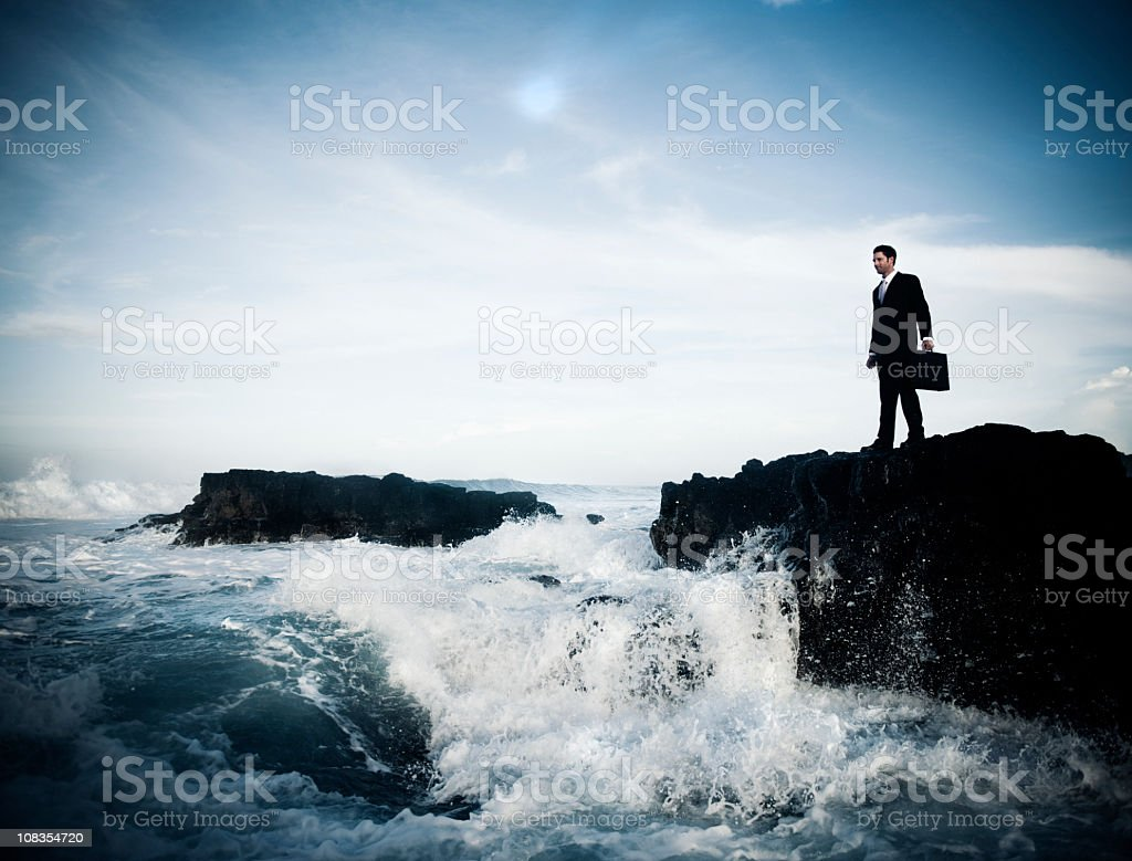Courageous businessman standing on rocks stock photo
