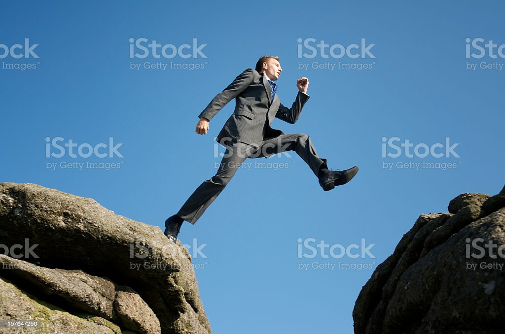 Courageous Businessman Taking Dangerous Step Across Valley stock photo