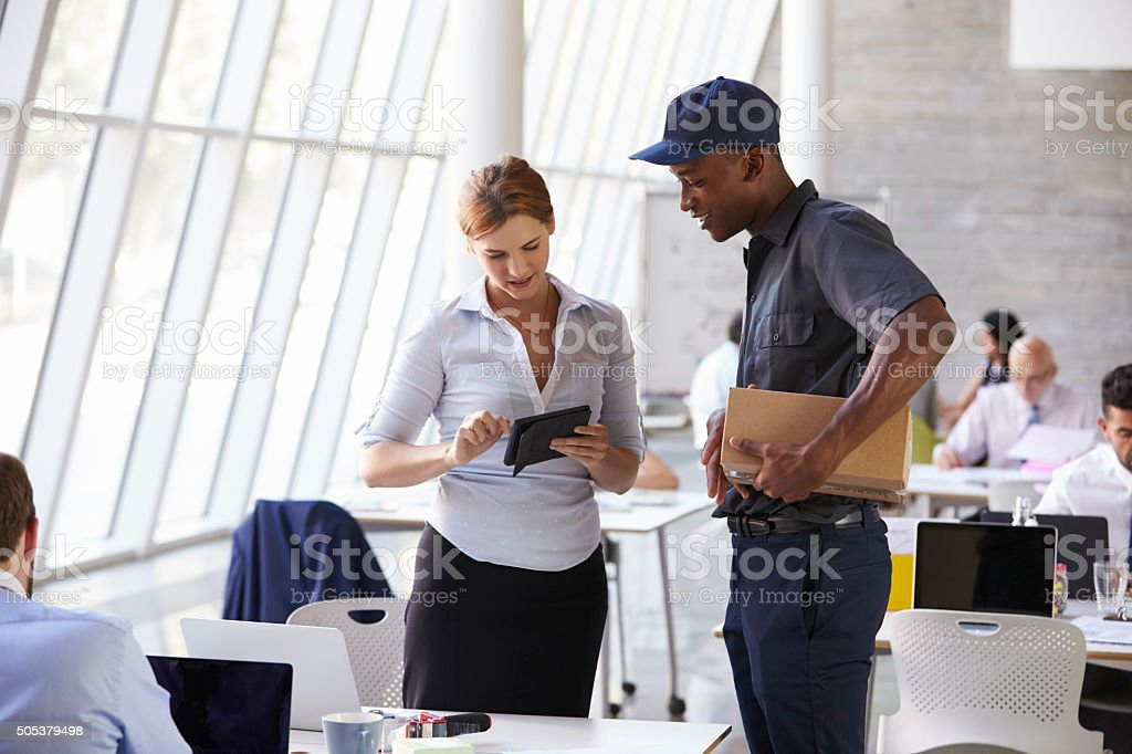Courier Collecting Package From Businesswoman In Busy Office stock photo