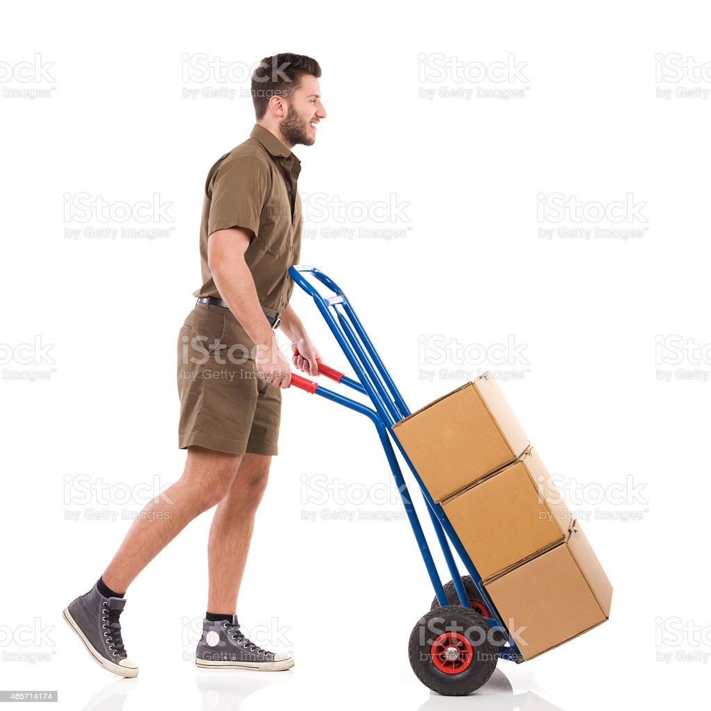 Courier walking with a delivery cart stock photo