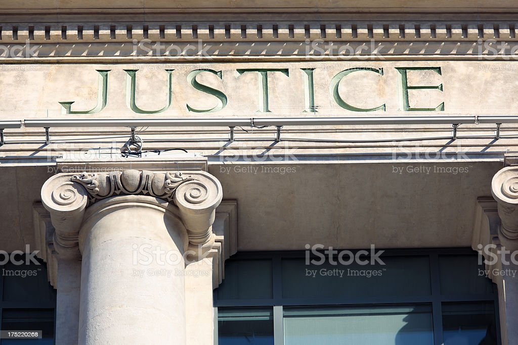 A courtroom building engraved with the word justice royalty-free stock photo
