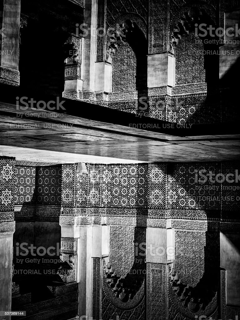 Courtyard carvings water reflexions in Ben Youssef Madrasa stock photo
