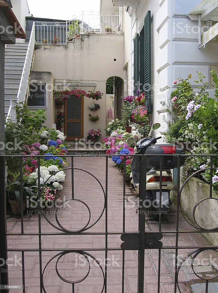 Courtyard with flowers and Scooter - Italy royalty-free stock photo