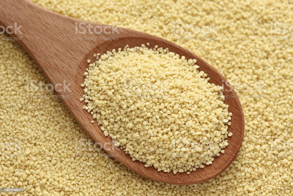 Couscous in a wooden spoon stock photo