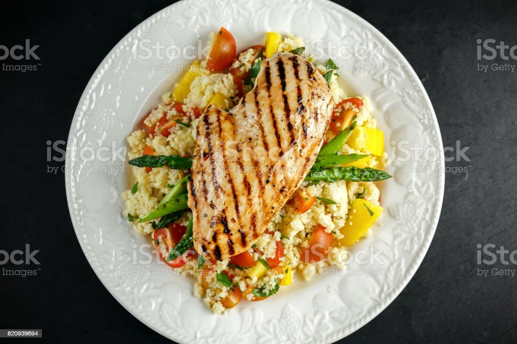 couscous salad with grilled chicken and asparagus on white plate. stone table. healthy food stock photo