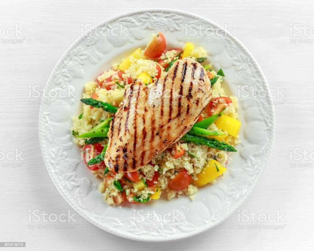 couscous salad with grilled chicken and asparagus on white plate. wooden table. healthy food stock photo