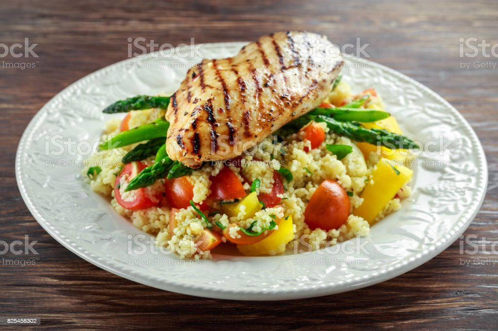 couscous salad with grilled chicken and asparagus on white plate. wooden rustic table. healthy food stock photo