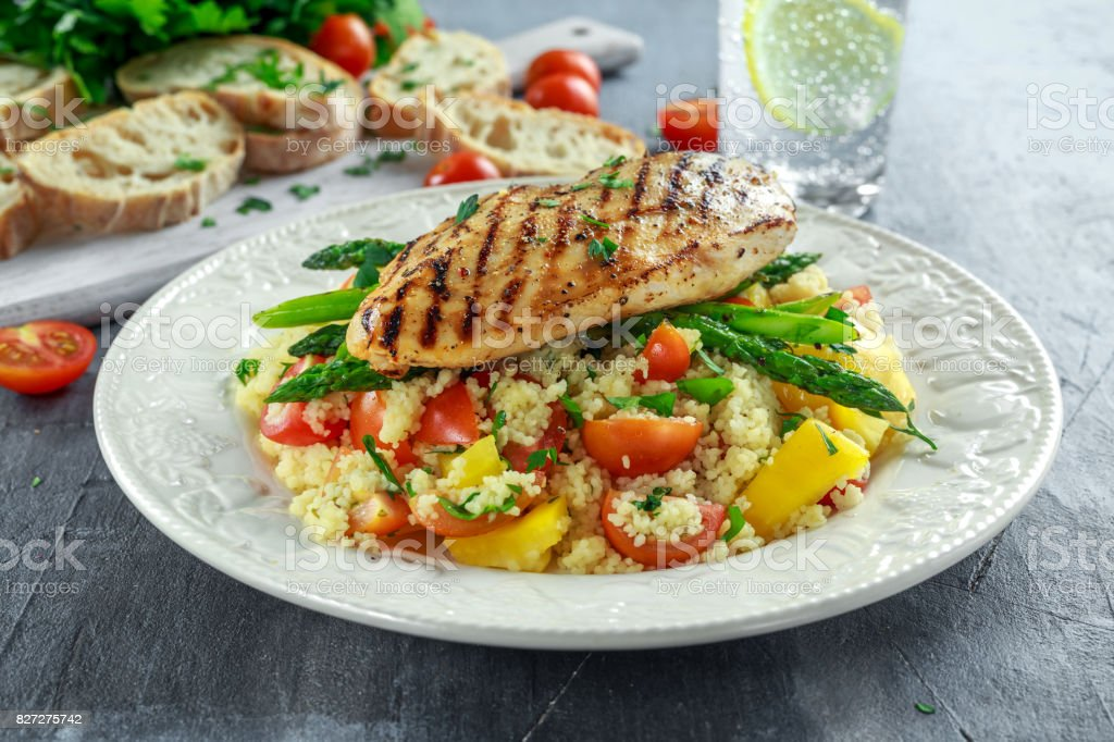 couscous salad with grilled chicken and asparagus on white plate. healthy food stock photo