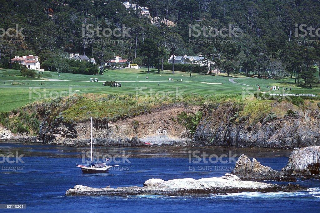 Cove With Sailboat at Pebble Beach, California stock photo