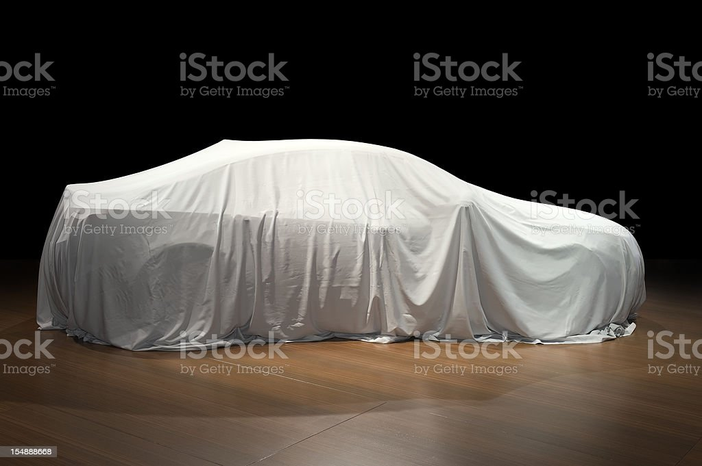 Covered car in exposition on wooden floor stock photo
