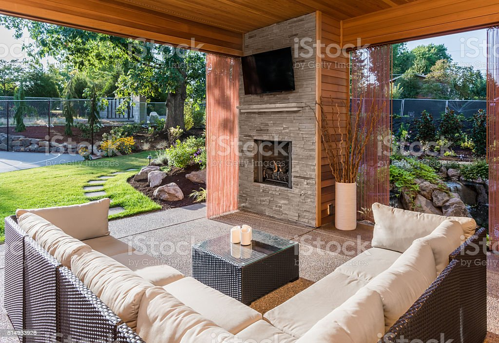Covered patio with fireplace, tv, and couch, with view of lush green...