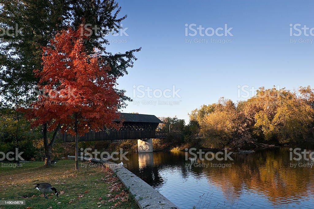 Covered walking bridge along river stock photo