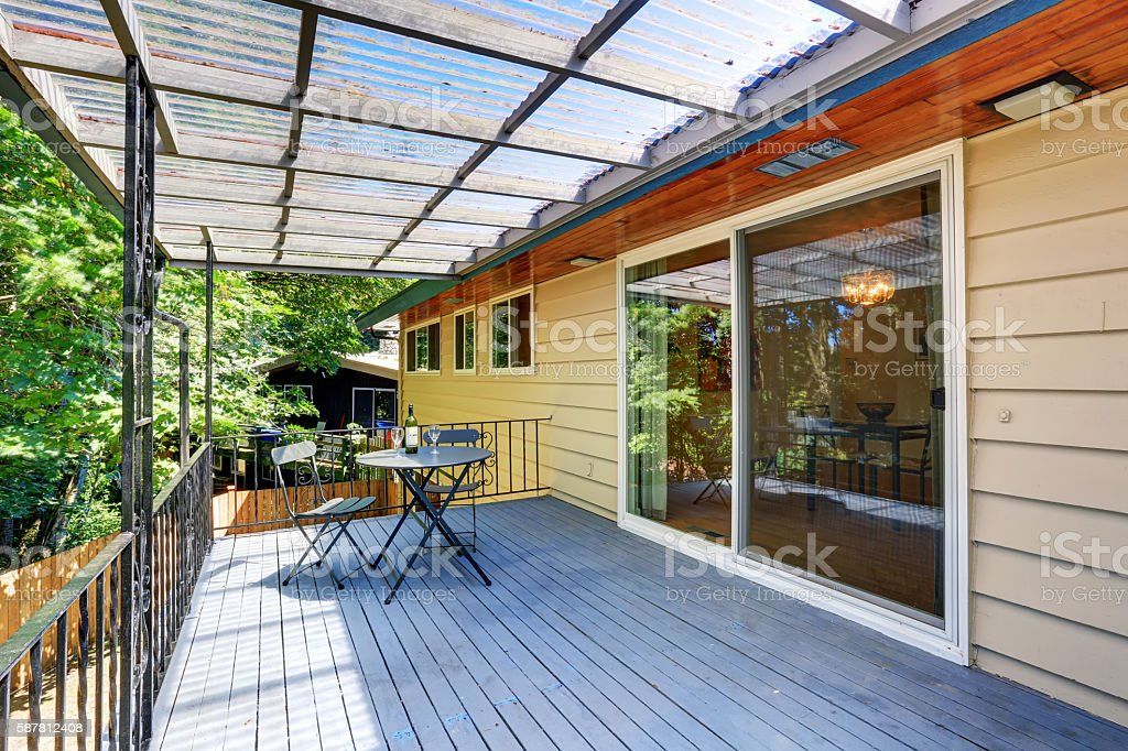 Covered walkout deck with metal railings and table set. stock photo