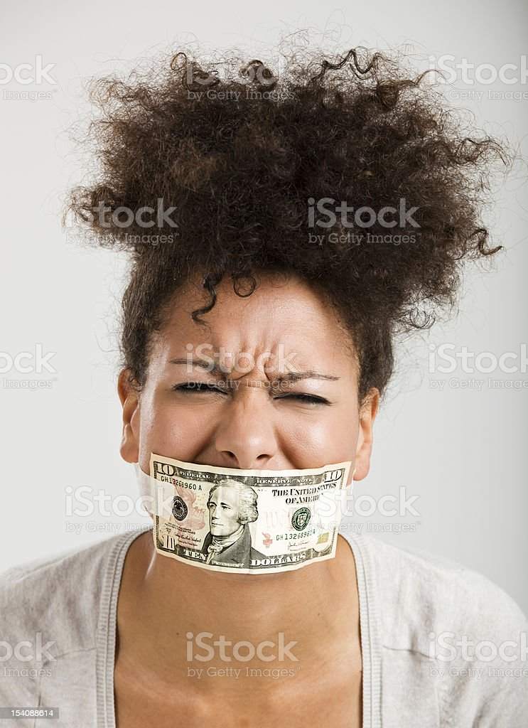Covering mouth with a dollar banknote stock photo