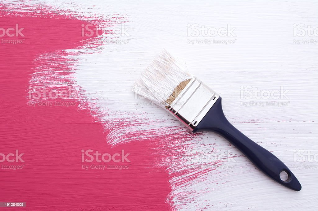 Covering pink paint with a coat of white emulsion stock photo