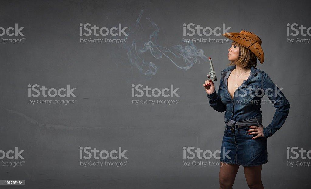 cow boy blowing on a smoking gun stock photo