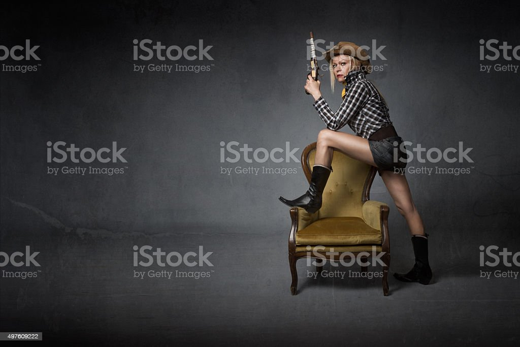 cow boy with gun standing near sofa stock photo