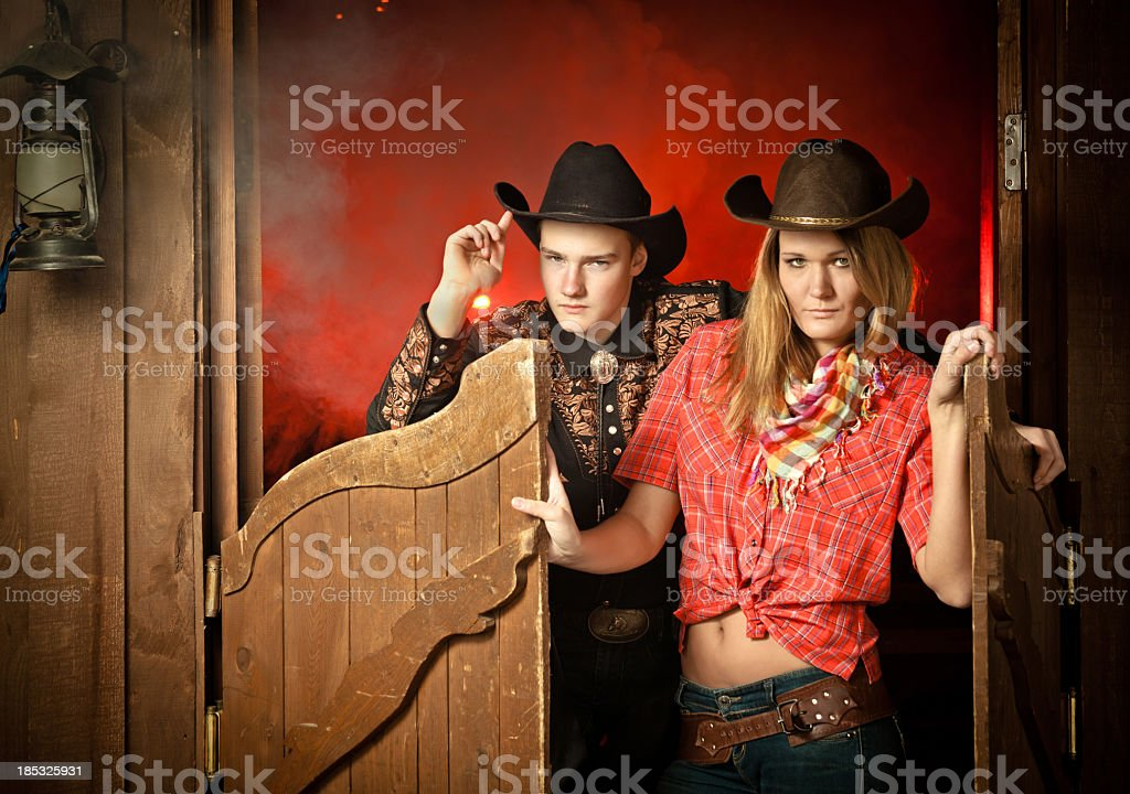 Cowboy and cowgirl couple at saloon doorway stock photo