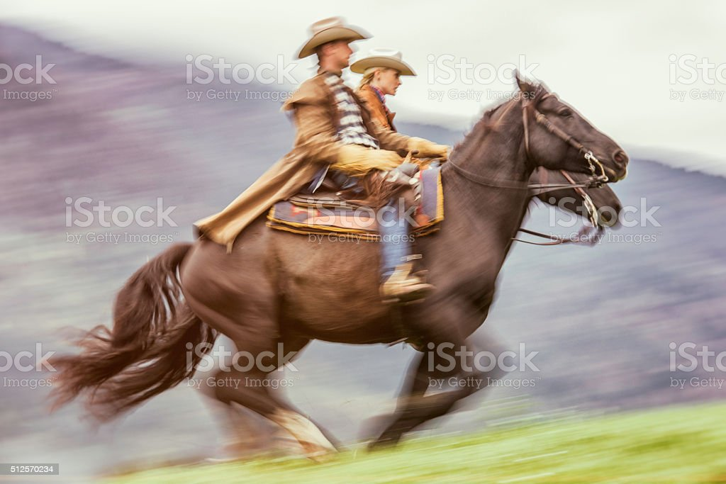 Cowboy and cowgirl galloping on a meadow stock photo