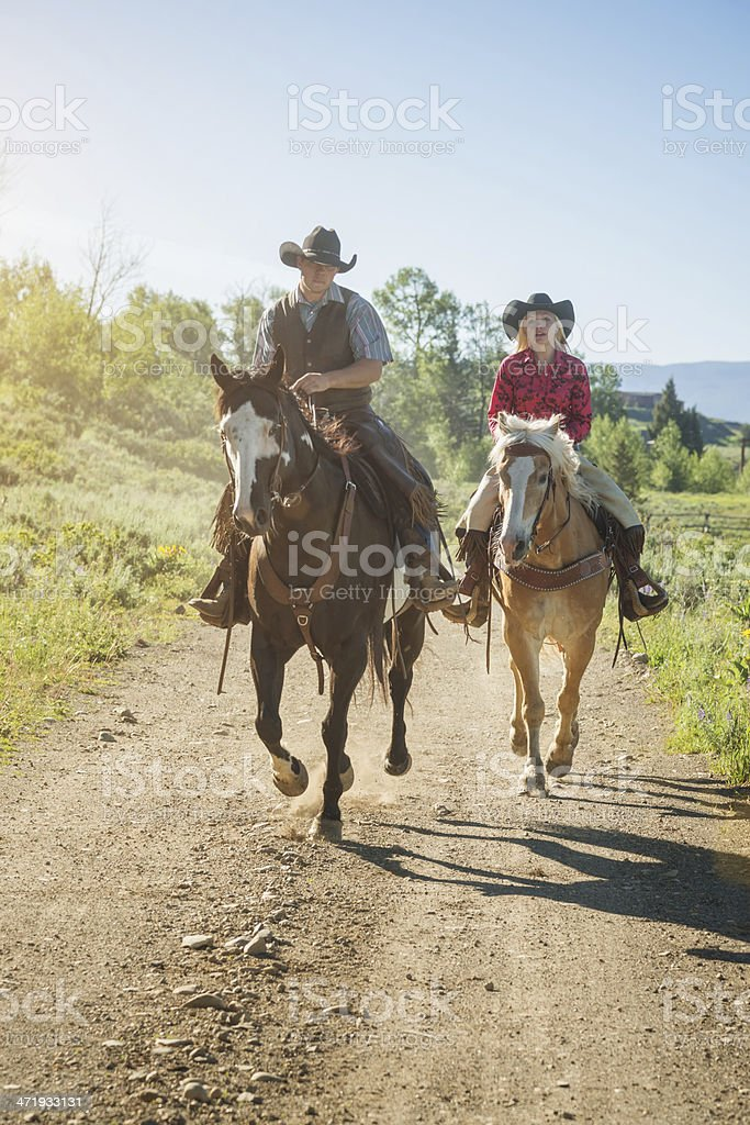 Cowboy and Cowgirl Horseback Riding stock photo
