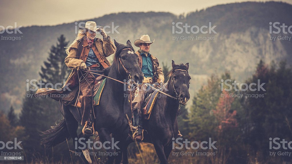 Cowboy and cowgirl riding on horses through the woods stock photo