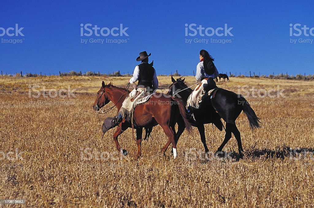 Cowboy and Cowgirl Riding Together, Ranch, Wild West, Couple, Copyspace stock photo