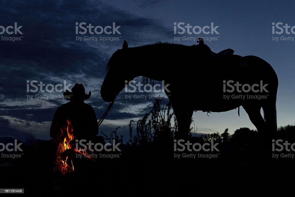 Cowboy and Horse Silhouette at a Campfire royalty-free stock photo