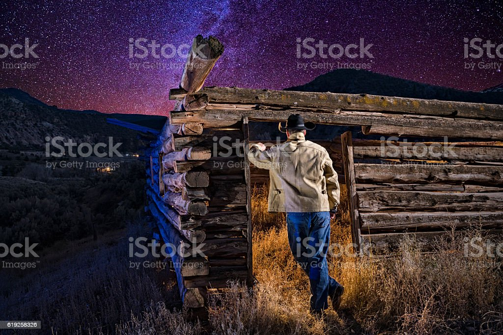 Cowboy and Old Cabin at Dusk with Stars stock photo