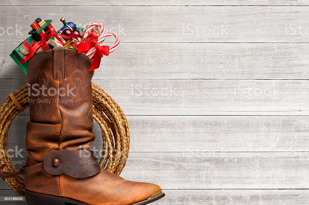 Cowboy Boot Stuffed With Presents In Front Of Whitewashed Boards stock photo