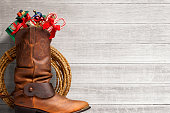 Cowboy Boot Stuffed With Presents In Front Of Whitewashed Boards