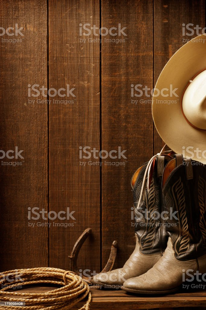 Cowboy boots, a cowboy hat, and lasso against barn stock photo