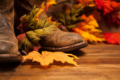 Cowboy boots among autumn leaves on wooden table.