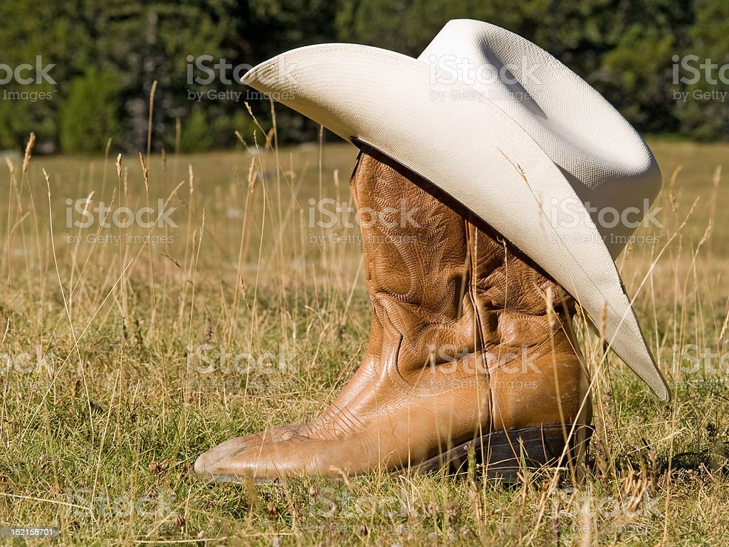 Cowboy boots and hat in the nature royalty-free stock photo