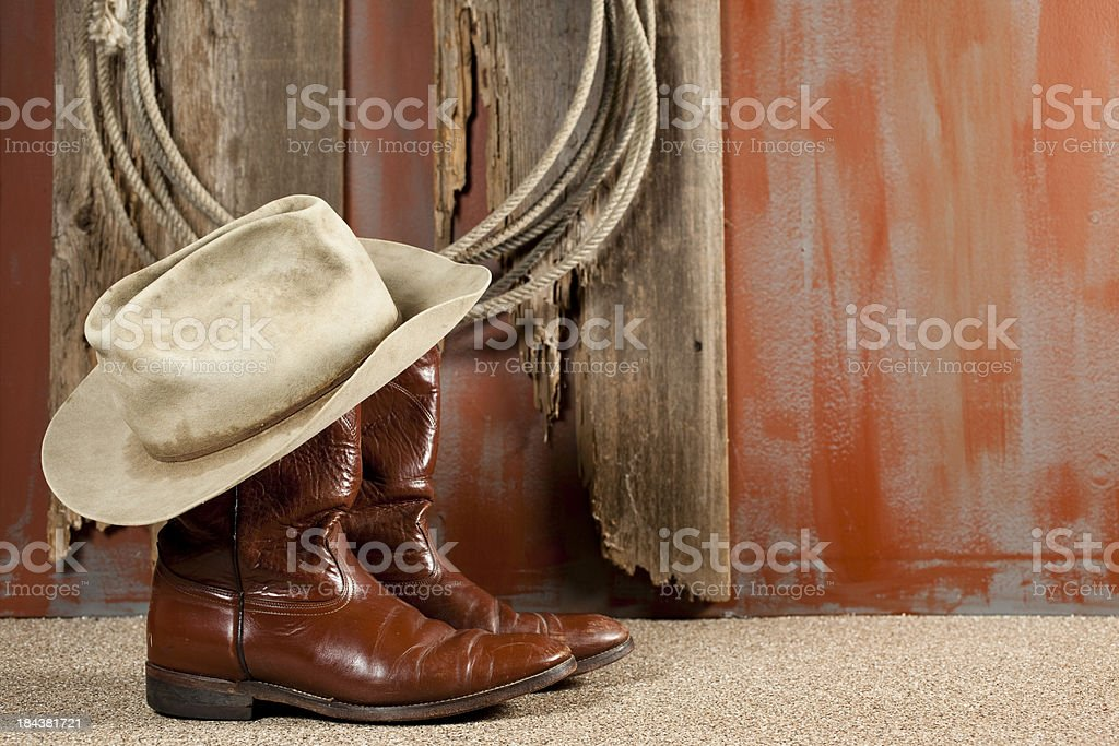 Cowboy boots and hat on rustic background royalty-free stock photo